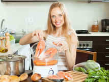 Woman cooking vegetables and salmon in electric steamer Royalty Free Stock Image