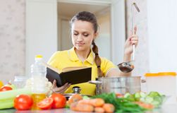 Woman cooking  veggie food with book Stock Photography