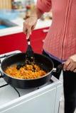 Woman cooking veggies in a pan Stock Image