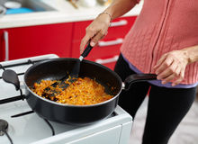 Woman cooking veggies in a pan Stock Photography