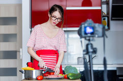 Woman cooking for Video-sharing website. Young caucasian blogger woman cooking at camera for Video-sharing website. Home location at kitchen Royalty Free Stock Photo