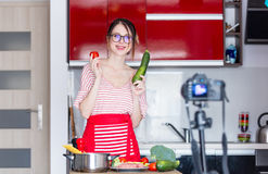 Woman cooking for Video-sharing website. Young caucasian blogger woman cooking at camera for Video-sharing website. Home location at kitchen Royalty Free Stock Photos