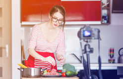 Woman cooking for Video-sharing website. Young caucasian blogger woman cooking at camera for Video-sharing website. Home location at kitchen Stock Photos