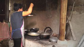 Woman cooks in a dirty kitchen in an old fashioned way. Full length stock video footage