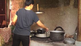 Woman cooks in a dirty kitchen in an old fashioned way. Full length stock footage