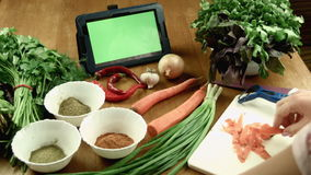The woman cooks food and watches the recipe in the tablet stock video