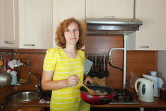 Woman cooks meat Royalty Free Stock Photos