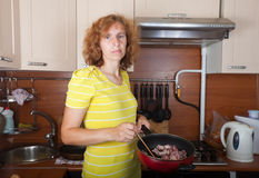 Woman cooks meat Stock Photo