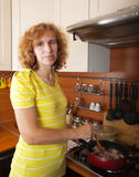 Woman cooks meat Stock Photography