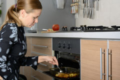 Woman cooks potatoes in the oven Stock Photos