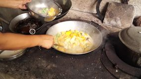 Woman cooks pumpkin in coconut milk in a dirty kitchen in an old fashioned way. Close up stock footage