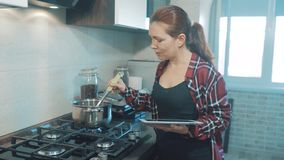 Woman cooks soup in the kitchen prevents the water in the pot and looks at the recipe on the digital tablet. woman in stock image