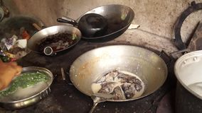 Woman cooks tuna fish in coconut milk in a dirty kitchen in an old fashioned way. Close up stock footage