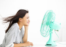 Woman cooling herself by electric fan. Smiling woman cooling herself by electric fan Royalty Free Stock Photography