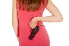 Woman cop pink dress gun back close Stock Image