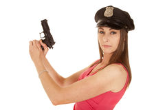 Woman cop pink dress gun side look Royalty Free Stock Photos
