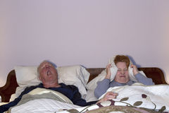 Woman Coping with Snoring Husband. Mature couple in bed with wife covering her ears to block out husbands snoring Stock Photo