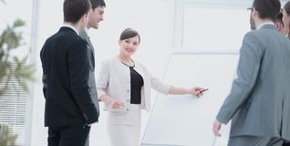 Copywriter and designers stand next to a blank poster and discus Stock Photos