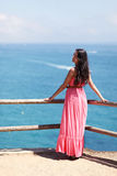 Woman in coral dress above sea. Beautiful young woman in pink coral long dress standing on cliff ledge near sea and looking at camera Stock Photos