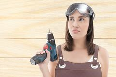 Woman with cordless drill ready for home repairs. Asian woman with cordless drill ready for home repairs. People holding electric tool. on wood background stock photos