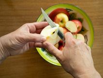 Woman Coring an Apple with a Tin Bowl with Apples in the Backgro stock photo