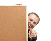 Woman with a corkboard. Closeup of a smiling young woman behind a corkboard pointing to us Stock Photos