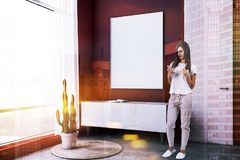 Red living room corner, poster and closet, woman. Woman in corner of loft living room with red walls, concrete floor, white and wooden closet with a book on it stock images