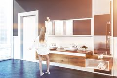 Woman in gray bathroom. Woman in corner of modern bathroom with white and gray walls, concrete floor, double sink standing on wooden countertop with vertical and royalty free stock photos