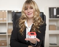 Woman in Corporate Attire Showing Model House. Curly haired Woman Sitting in Corporate Attire Showing Model House on Palm Stock Images