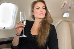 Woman in a corporate jet drinking a glass of champagne Royalty Free Stock Image