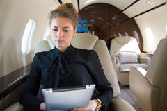 Woman in corporate jet looging at tablet computer Royalty Free Stock Photography