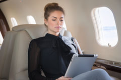 Woman in corporate jet looging at tablet computer Royalty Free Stock Images