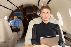 Woman in corporate jet looking at tablet computer Stock Photography