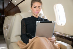 Woman in corporate jet looking at tablet computer Royalty Free Stock Images