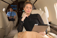 Woman in corporate jet looking at tablet computer Stock Image