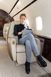Woman in corporate jet looking at tablet computer Stock Photo
