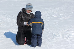 Woman correcting clothes to a child in the snow. In winter Stock Image