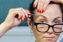 Woman correcting eyebrows Royalty Free Stock Photography