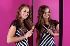 Woman correcting hairs at mirror Stock Photos