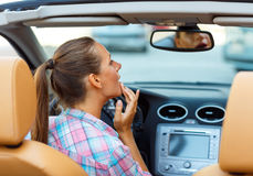 Woman corrects makeup looking in the rearview mirror in a conver Stock Photos
