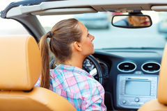 Woman corrects makeup looking in the rearview mirror in a conver Royalty Free Stock Image