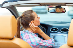 Woman corrects makeup looking in the rearview mirror in a conver Stock Photography