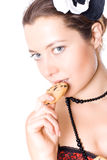 Woman in corset and little hat eating cookie Royalty Free Stock Photography