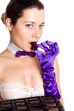 Woman in corset and little hat eating sweets Stock Images