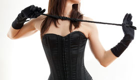 Woman in a corset and  riding crop Royalty Free Stock Photography