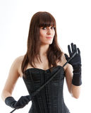 Woman in a corset and  riding crop Stock Images