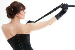 Woman in a corset and whip Stock Images