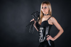 Woman in a corset with a whip. Beautiful woman in a corset with a whip in hands Royalty Free Stock Image