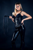 Woman in a corset with a whip in hands Stock Photo