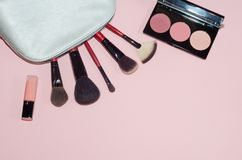 Woman cosmetic bag, make up beauty products on pink background. Makeup brushes, pink lipstick and rouge palettes. Decorative cosme. Tics. Top view, flatlay Stock Images